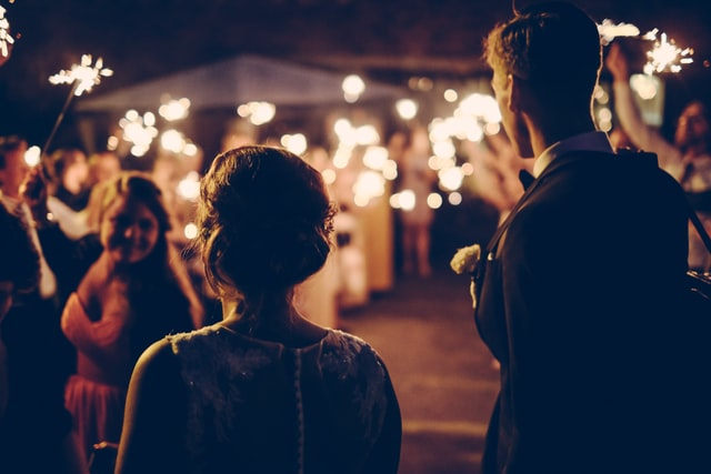 man and woman seeing a friend with fireworks in her hand