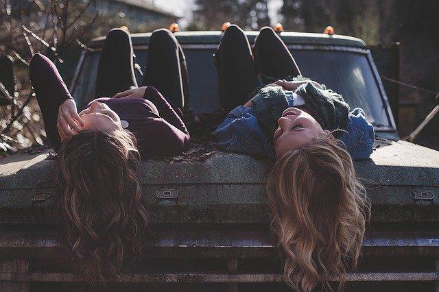 girls lying on a car