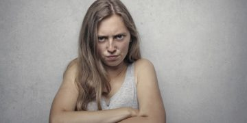 woman in gray tank top looking furious