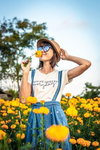 woman holding a hat and smelling a yellow flower