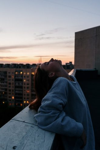 woman in blue hoodie standing at the top of the building