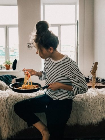 woman in black and white striped shirt eating food from pot