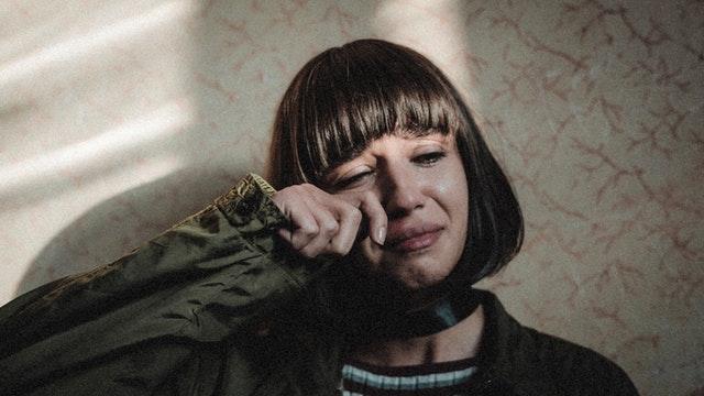young sad woman crying at home