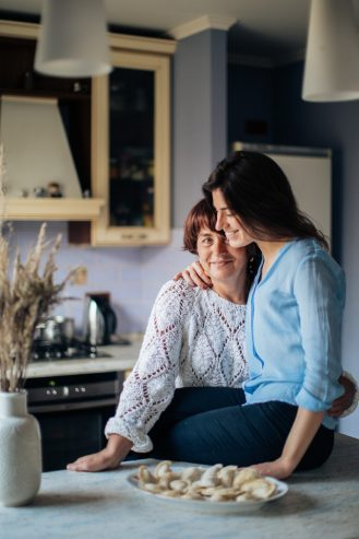 woman in white long sleeve shirt hugging her daughter