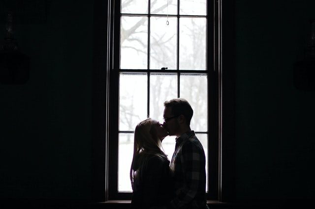 man and woman kissing beside a window