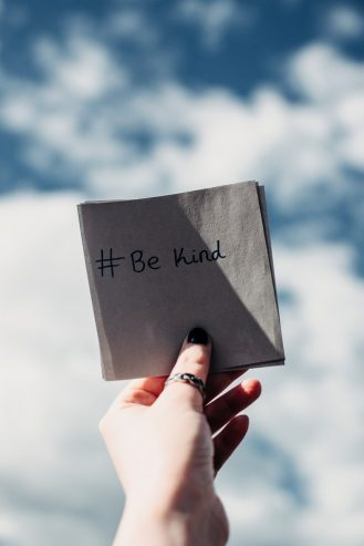 person holding a be kind note