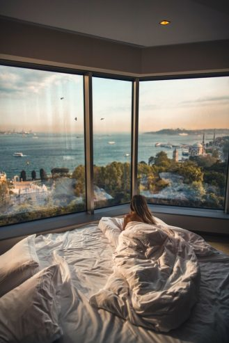 woman laying down in bed while looking at the view outside