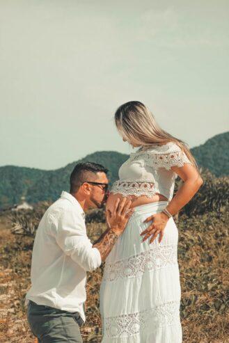man wearing white dress shirt kissing woman on her baby bump