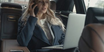 a woman in corporate attire answering a call in her car with laptop on her lap