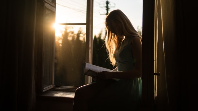 woman reading a book at the window