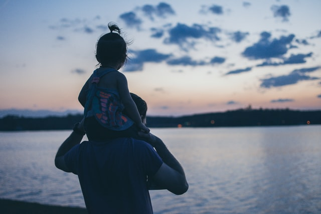man carrying his daughter on his shoulder looking at the sea
