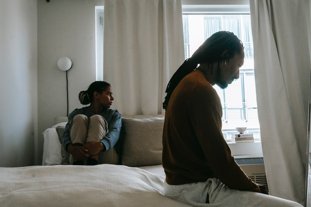 sad african american couple during quarrel on bed