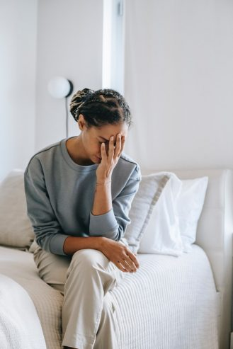 anxious black woman covering face with hand on bed