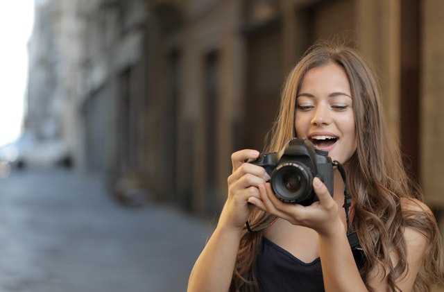woman in black tank top holding a black DSLR