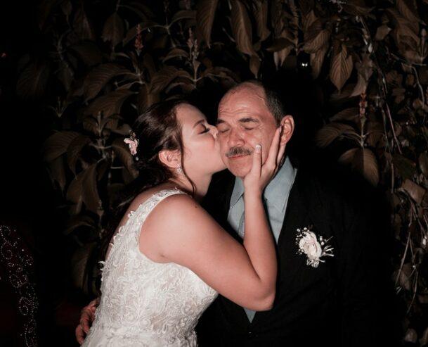 elegant bride kissing father on wedding day