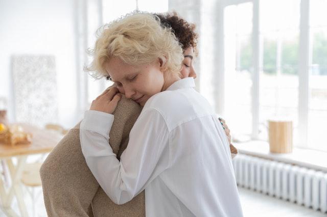 multiracial women hugging tenderly