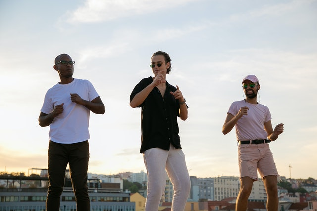 young diverse guys dancing on building roof during party