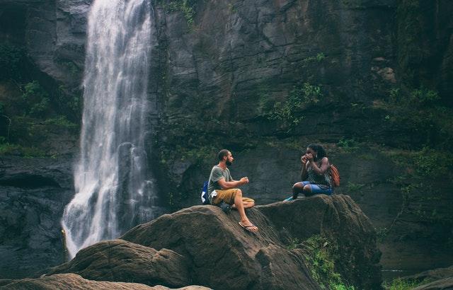 man and woman near a waterfall