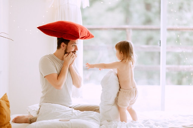 man with red pillow on his head with his kid on bed