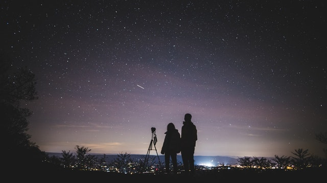 silhouette of two person standing during night time