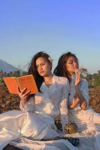 woman reading a book beside another woman holding a flower